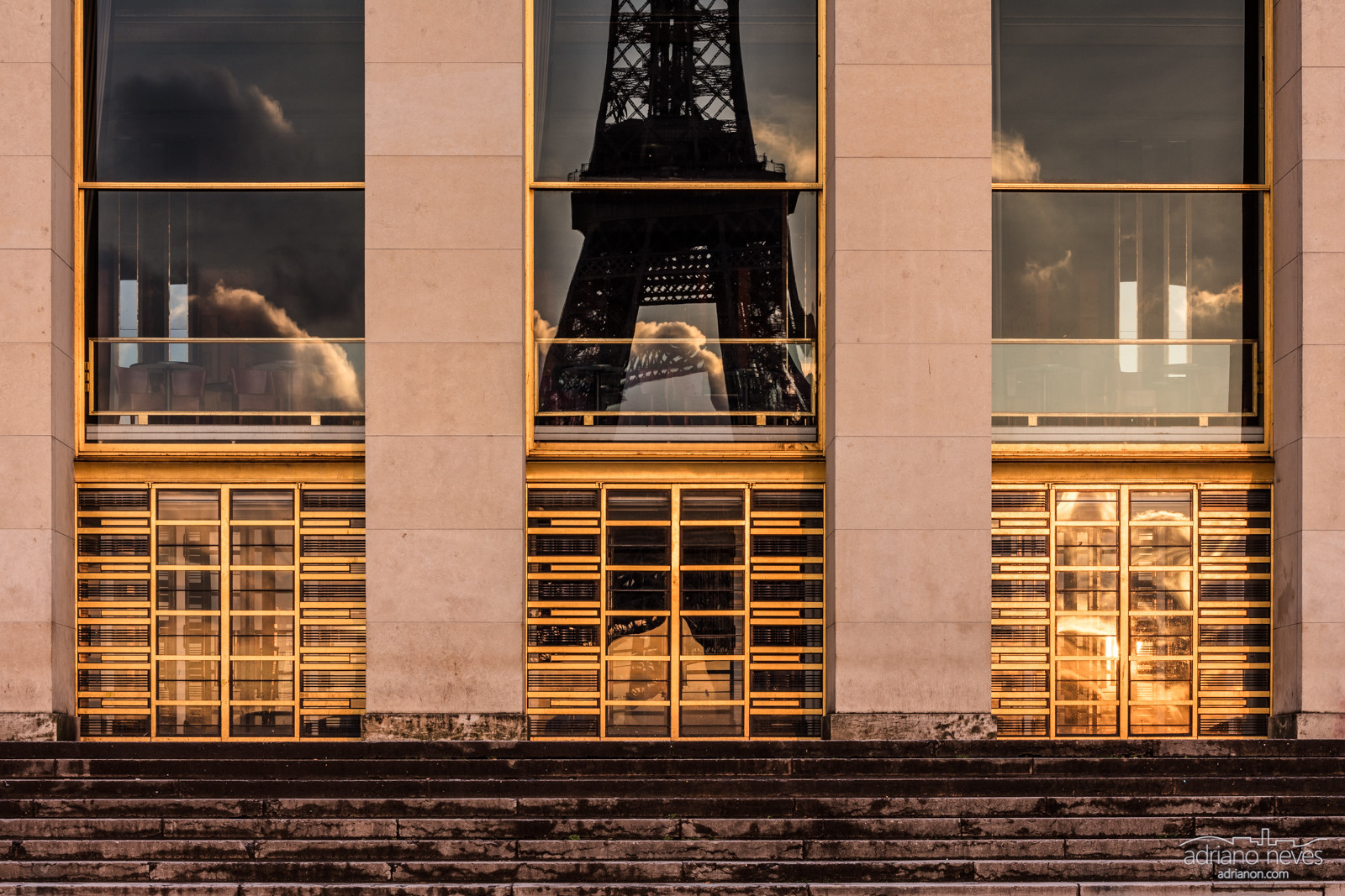 Early morning view of gilded facade at the Trocadero monument, Paris, France, and the Eiffel Tower reflected in the windows.